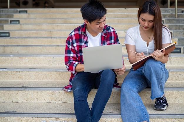 Азиатские студенты мужского и женского пола сидят и рассматривают учебник, обсуждают учебу, в свободное время делают домашние задания на территории школы.