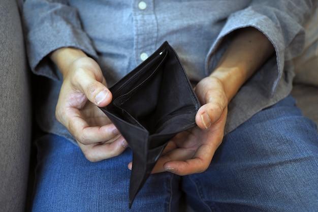男の手が請求書やクレジットカードの支払いに空の財布、貧困、債務と破産を開きます