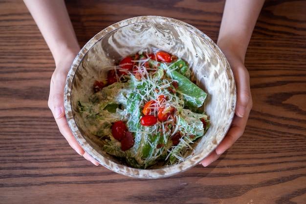 木製のボウルに野菜のサラダ。女性の手は、体に健康的な食品を選び、野菜や果物を食べるサラダを示しています。良い減量ガイドライン。
