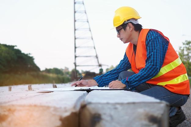 エンジニアは建築現場の杭に置かれている青写真を読んでいます