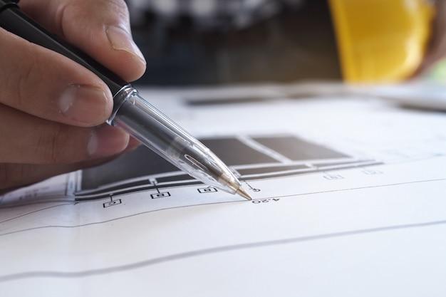 チーフエンジニアがペンを手に持って建物の青写真をチェック