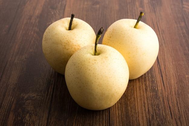 木製のテーブルの上に黄色のリンゴ