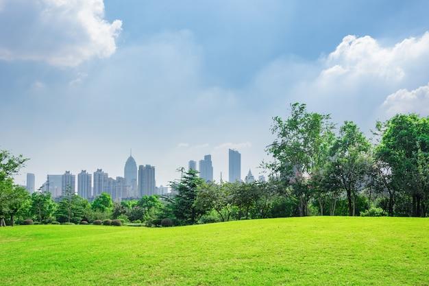 背景にあるダウンタウンのスカイラインと青空の下で都市公園