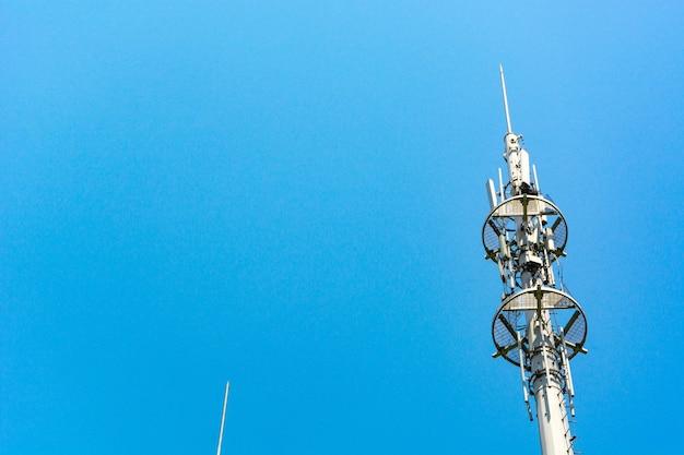 Красно-белая башня связи с множеством разных антенн под голубым небом и облаками