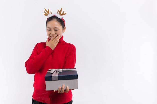 伝統的な冬の休日。クリスマスのストッキングのコンセプト。クリスマスストッキングの内容を確認してください。サンタの帽子の女性はクリスマスプレゼントを保持します。