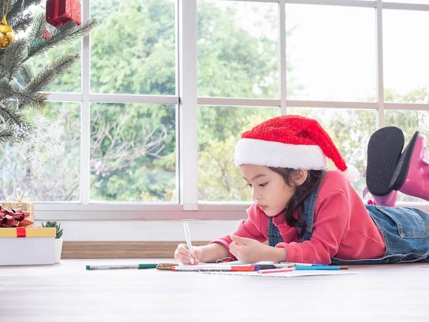 Очаровательная маленькая милая девушка рисует в открытку деду морозу