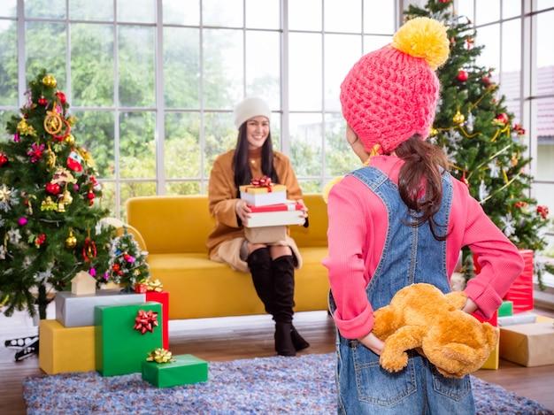 クリスマスの日に彼女の母親にテディベアギフトを与えるかわいい女の子。クリスマスのお祝いのコンセプト。