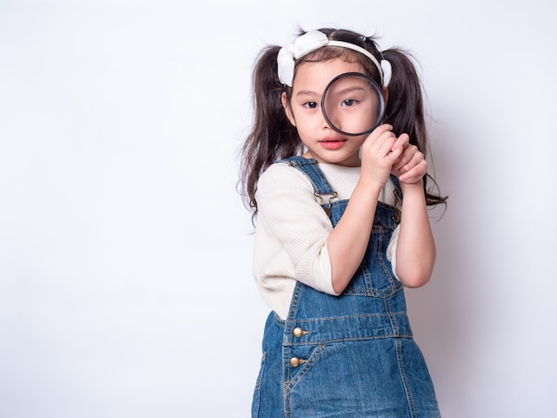 虫眼鏡を押しながら見ているアジアのかわいい女の子。虫眼鏡を見て小さな女の子