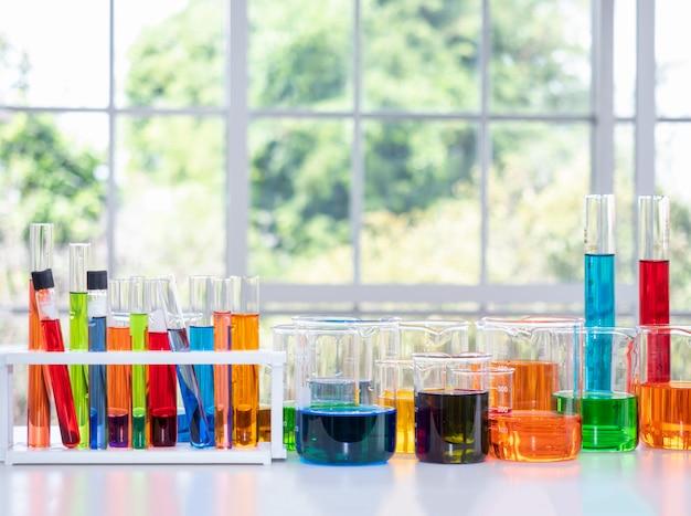 ぼやけた窓ガラスを備えた科学実験室で多色のソリューションを使用して、白いテーブルのチューブとビーカーに近づきます。
