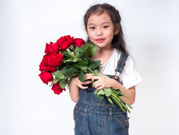 Счастливая азиатская маленькая милая девушка стоя и держа букет красной розы.