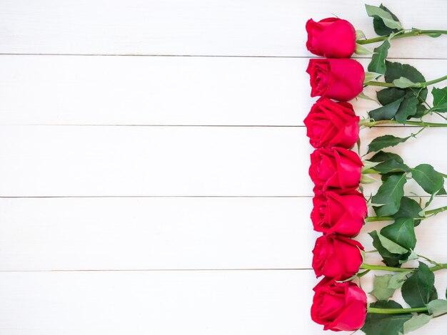 コピースペースを持つ白い木製プレートに赤いバラの花。上面図