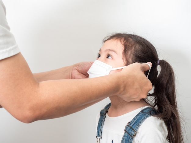 Отец надевает гигиеническую маску своей дочери для защиты от вирусов, простуды или загрязнения