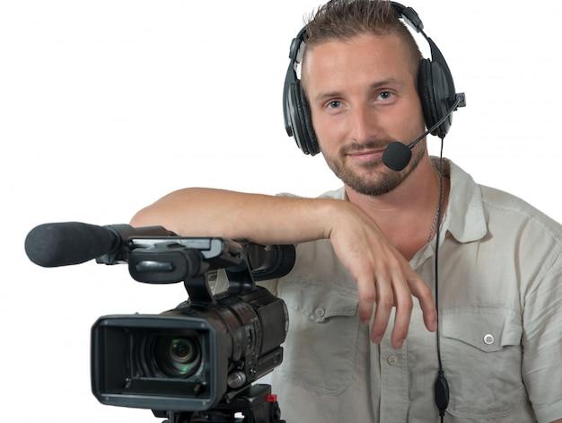 プロのビデオカメラと白で隔離されるヘッドフォンとカメラマン