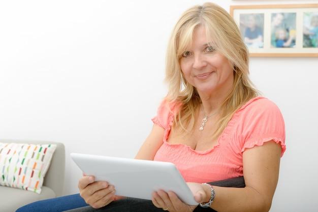 自宅で電子タブレットを使用して美しい熟女