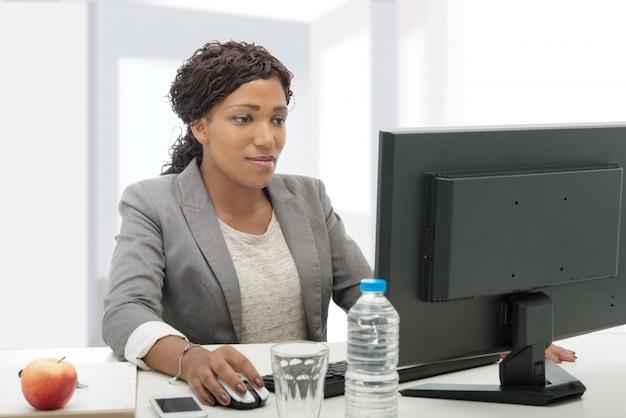 アフリカ系アメリカ人ビジネスの女性がコンピューターで作業して