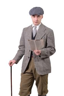 Молодой человек в винтажной одежде с шляпой, читая газету