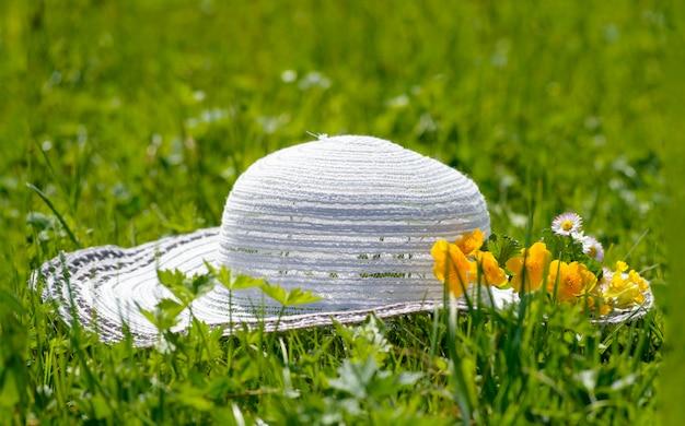 Женская шляпа в траве с цветами