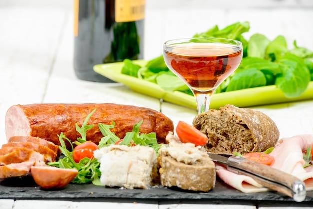 Холодная мясная тарелка с бокалом вина
