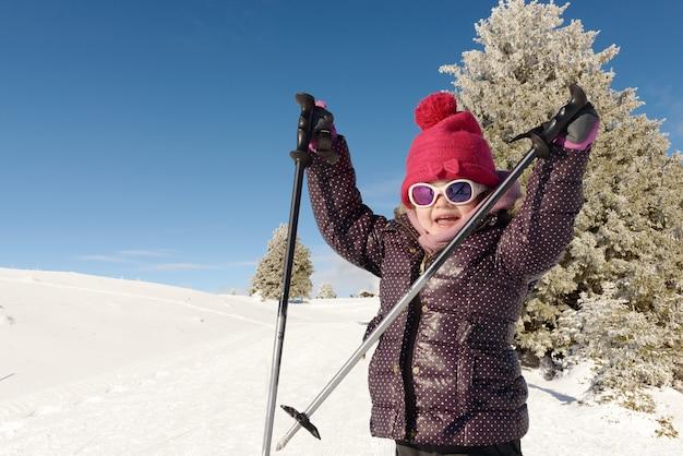 下り坂のスキーの幸せな女の子