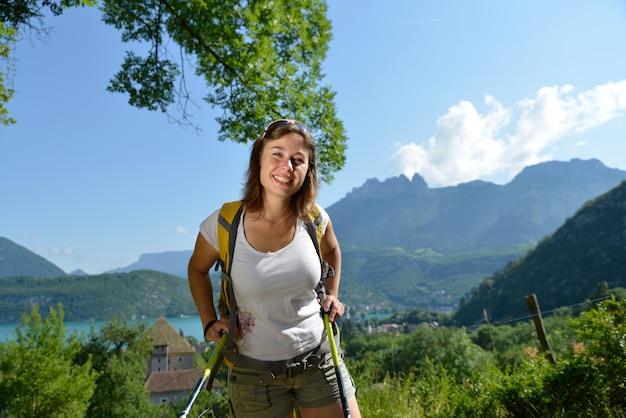 若い女性はアルプスでハイキングします。