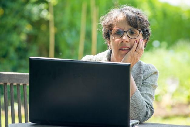 Зрелая брюнетка с ноутбуком в саду