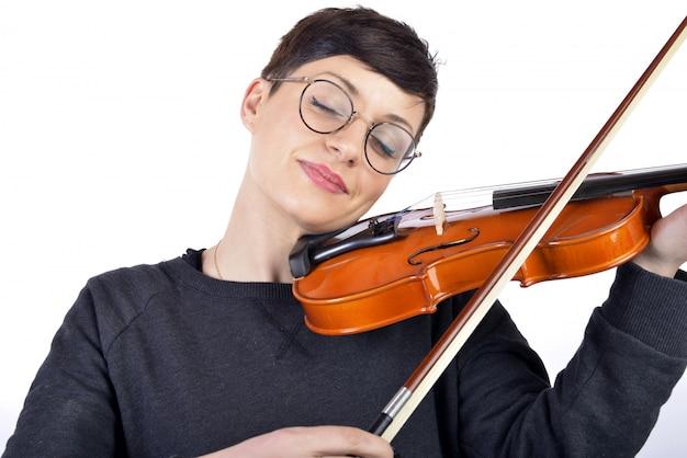 表情で彼女のバイオリンを弾く若い女性
