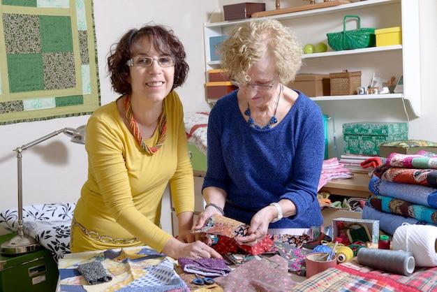 Две женщины работают над своим одеялом