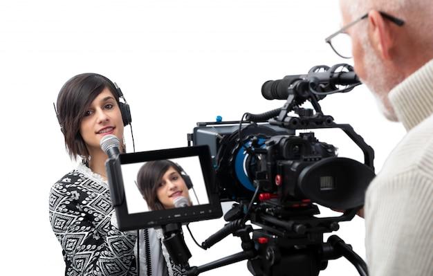 Милая журналистка молодой женщины представляя репортаж в студии телевидения на белизне