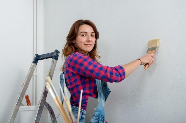 Милая молодая женщина красит стену в белый цвет