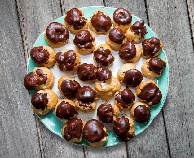 チョコレートで覆われたバニラクリームペストリーパフクローズアップ。