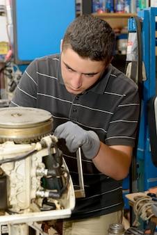 若い男のメカニックがモーターボートの修理