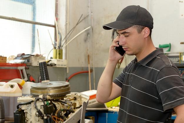 若い男のメカニックがモーターボートと顧客で電話を修復