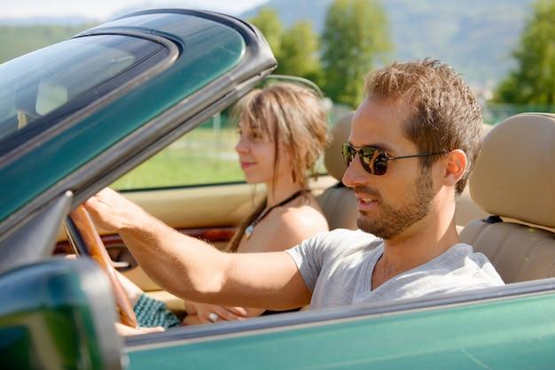 コンバーチブル車の若いカップル