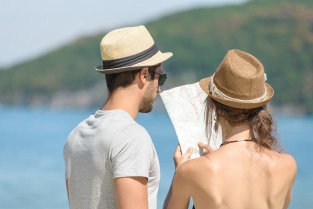 Молодая пара на отдыхе, глядя на карту