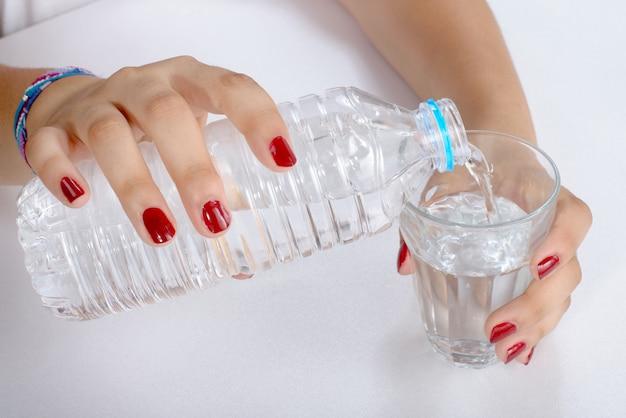 Молодая женщина наполнила стакан водой