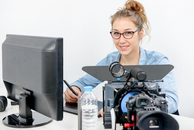 ビデオ編集用のグラフィックタブレットを使用して若い女性デザイナー