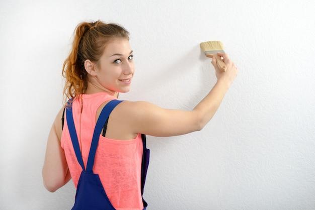 かなり若い女性が壁に白い色を塗る