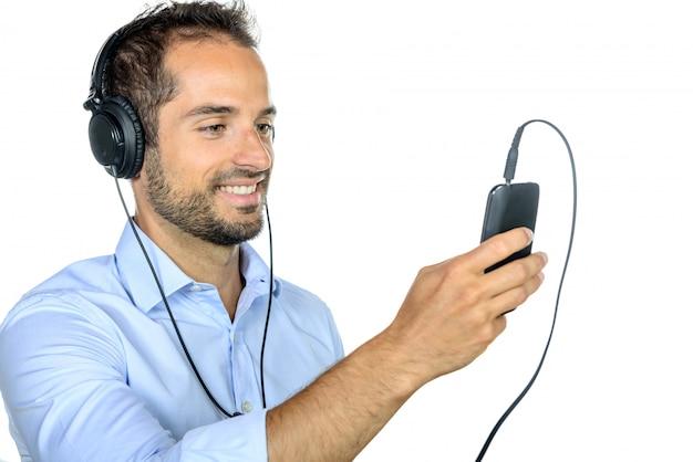 若い男が彼の携帯電話で音楽を聴く