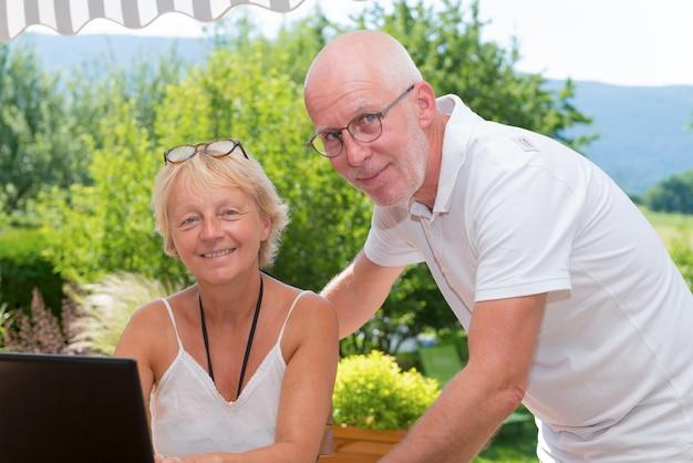 自宅でラップトップコンピューターを使用して年配のカップル