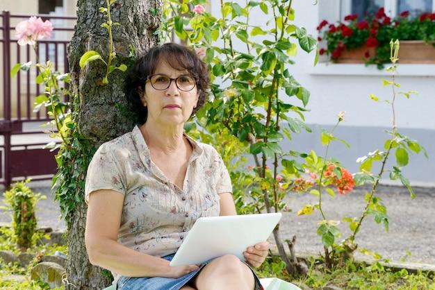 庭でタブレットで座っている熟女