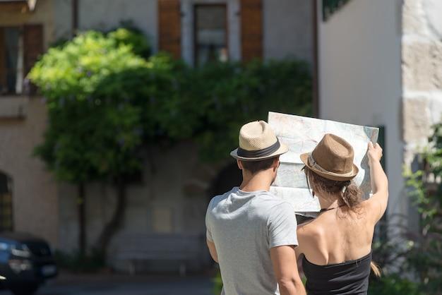 Молодая пара в отпуске смотрит на карту