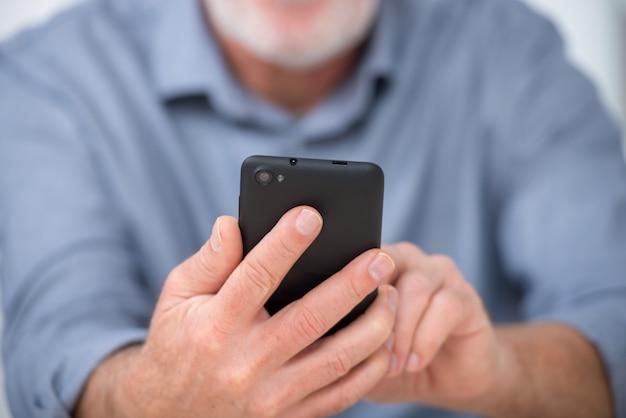 自宅でスマートフォンを使用して成熟したハンサムな男