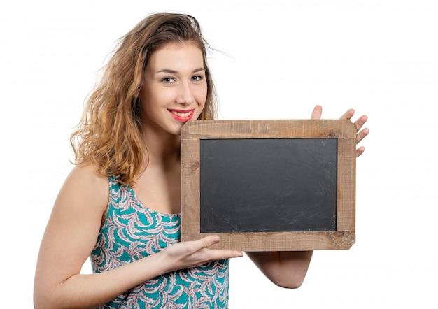 Милая молодая женщина показывая малую доску изолированную на белизне