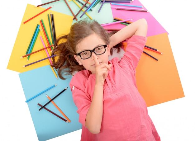 色鉛筆で床に横たわって学校の女の子