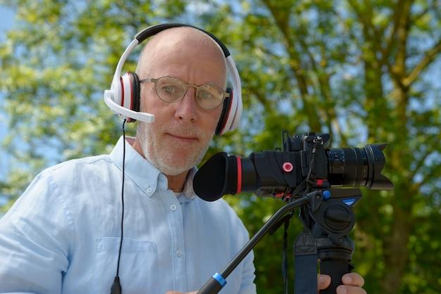 カメラのデジタル一眼レフを使用して、ヘッドフォンを持つ男