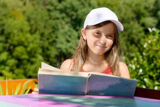白い帽子の少女は、外で本を読みます