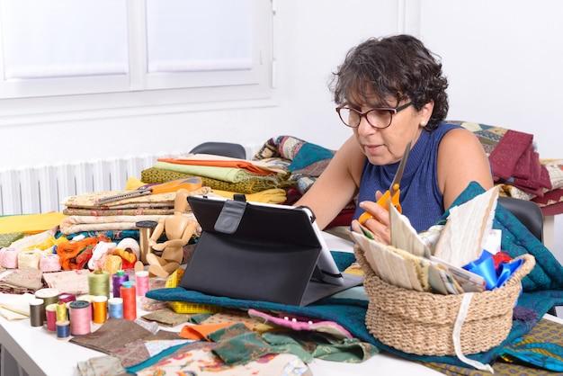 タブレットコンピューターを使用して美しい成熟した女性の裁縫師