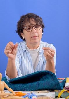 成熟したブルネットの女性縫製パッチワーク