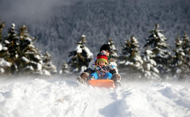 Маленький мальчик катается на санках по снегу