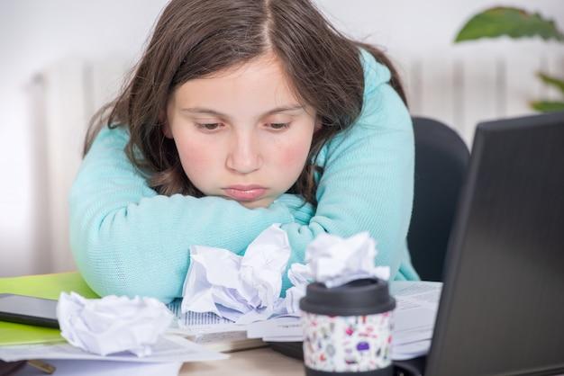 Скучающая девочка-подросток делает свою домашнюю работу
